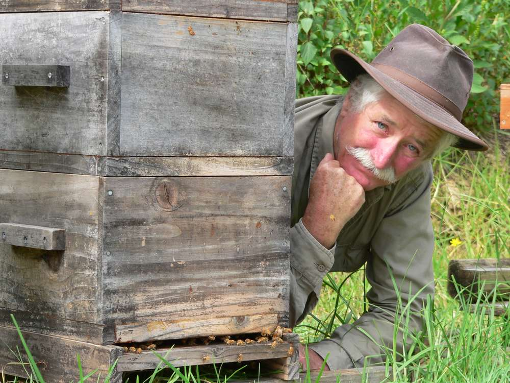 Bryan Divers, co-founder of Mamaki Farm and Village, poses with one of his Warre beehives.