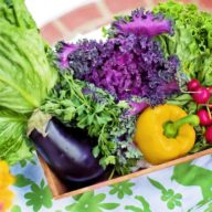 Fresh summer vegetables in a box on a bright tablecloth.
